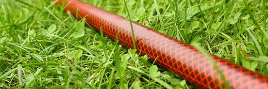 braided water hose in grass